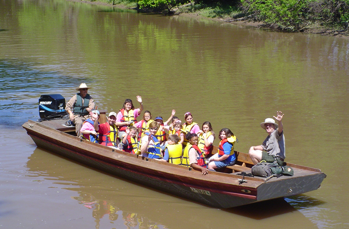 Image of park ranger and visitors in an open boat on the bayou