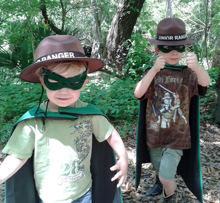 Image of two little boys dressed as wetlands superheroes and wearing Junior Ranger hats