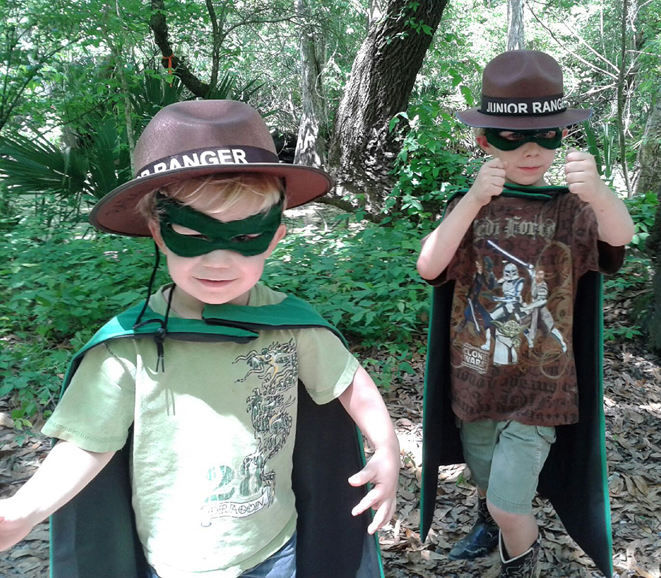 Two little boys wearing Junior Ranger hats and superhero capes