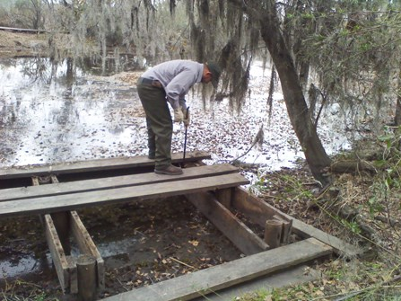 Image of man working on a wooden platform that will become a canoe dock