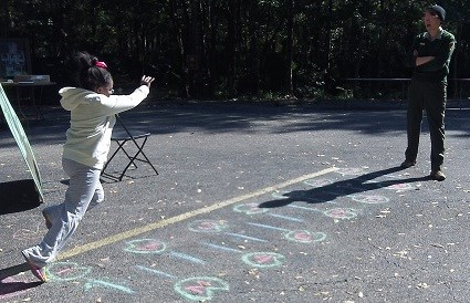 A female ranger watches as a young girl leaps across chalk lines on pavement