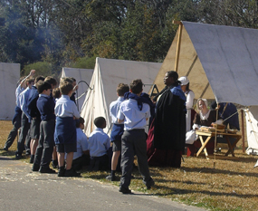 A woman dressed in 1815-era clothes talks to children