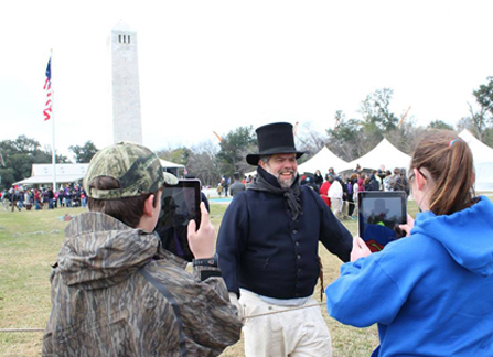 Image of students with digital tablets taking pictures of man dressed as War of 1812 sailor