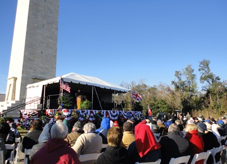 Image of people in chairs looking at stage decorated with flags and bunting