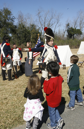 A man dressed as an 1815 soldier talks with children