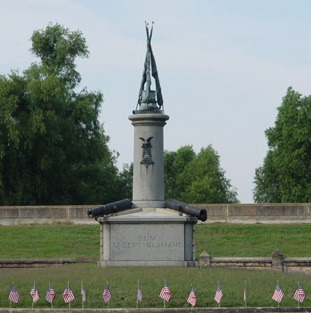 Image of Civil War-era memorial with crossed rifles at top and row of small American flags in front