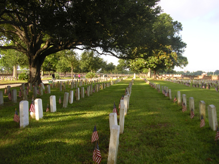 Image of row of headstones, each with a flag, in Chalmette National Cemetery