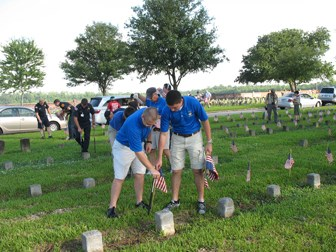 Image of people putting American flags at graves in Chalmette National Cemetery
