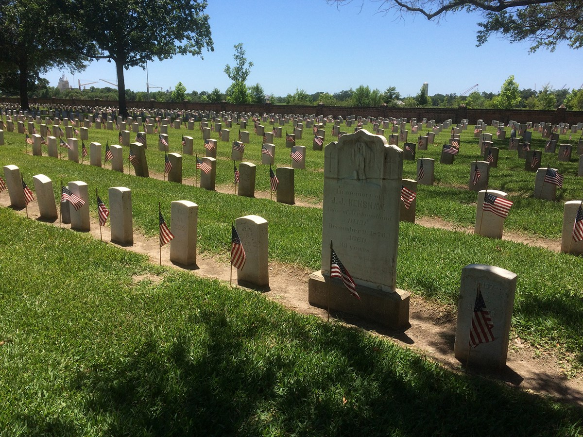 Rows of national cemetery headstones with an American flag in front of each