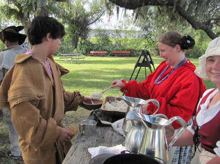 Image of young women in 1815 dress serving lunch to young men in period militia clothes