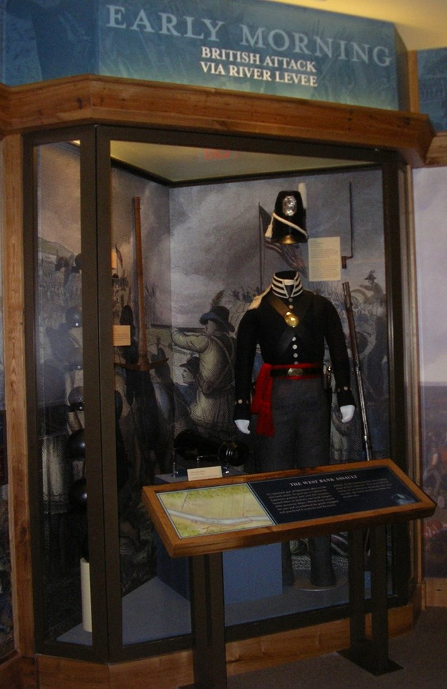 Glass exhibit case with 1815 American uniform and cannonballs