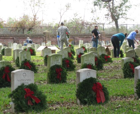 Image of people placing evergreen wreaths at headstones in Chalmette National Cemetery