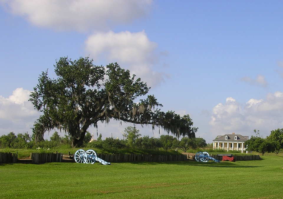 Cannons at a rampart with a historic home in background