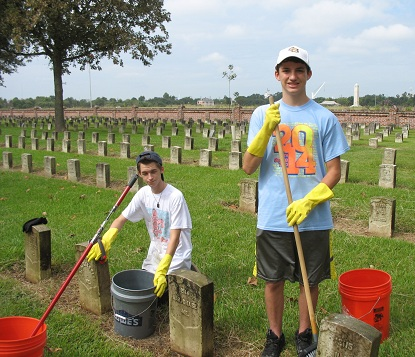 Two young men clean headstones at Chalmette National Cemetery