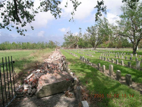 Brick wall at Chalmette National Cemetery lies in ruins after Hurricane Katrina in 2005.
