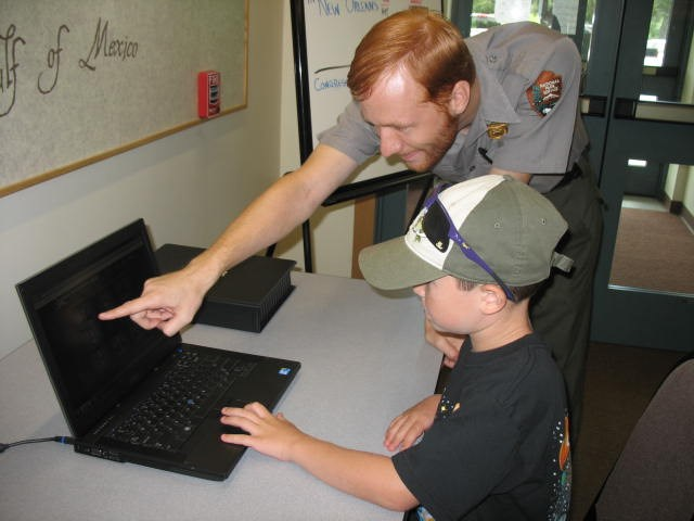 Image of ranger and young boy at computer
