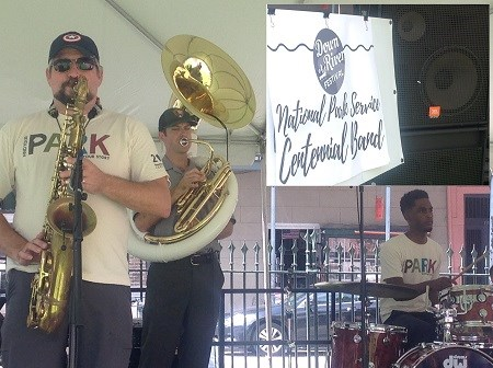 "A drummer, a saxophone player, and a sousaphone player are performing, wearing ""Find Your Park"" shirts."