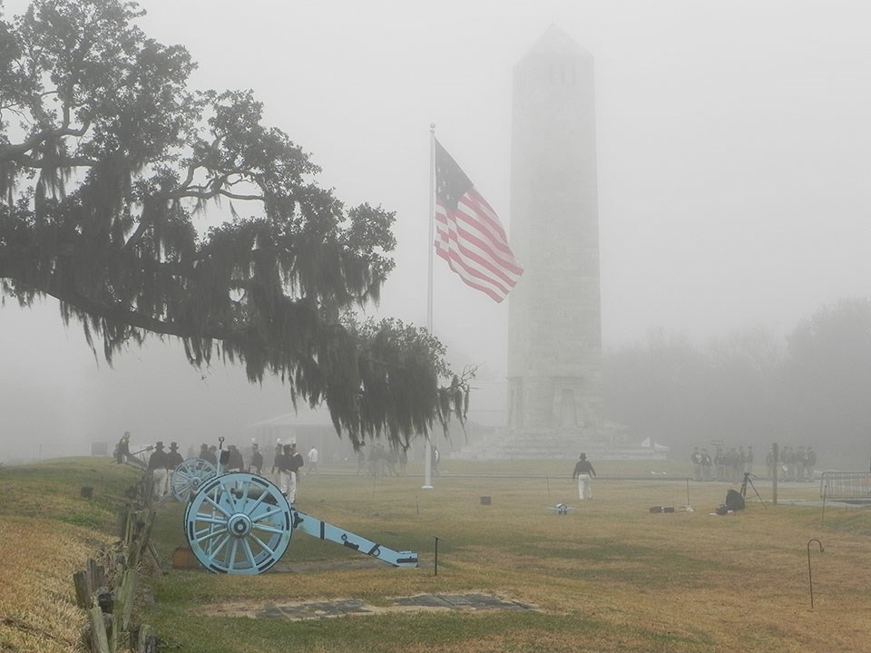 Cannons, an American flag, and Chalmette Monument in the fog