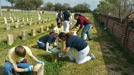 Volunteers with brushes and buckets cleaning military headstones in a cemetery