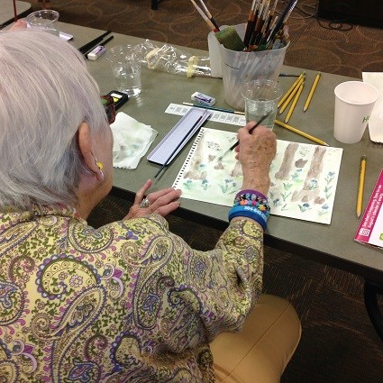 A woman holding a brush paints a scene of a cypress swamp with watercolor paints