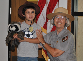 A park ranger and a little boy in a Junior Ranger hat