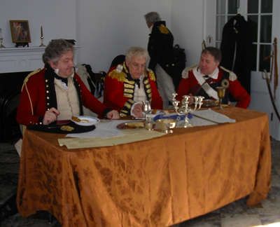 Three British officers in red coats seated at a table, examining maps
