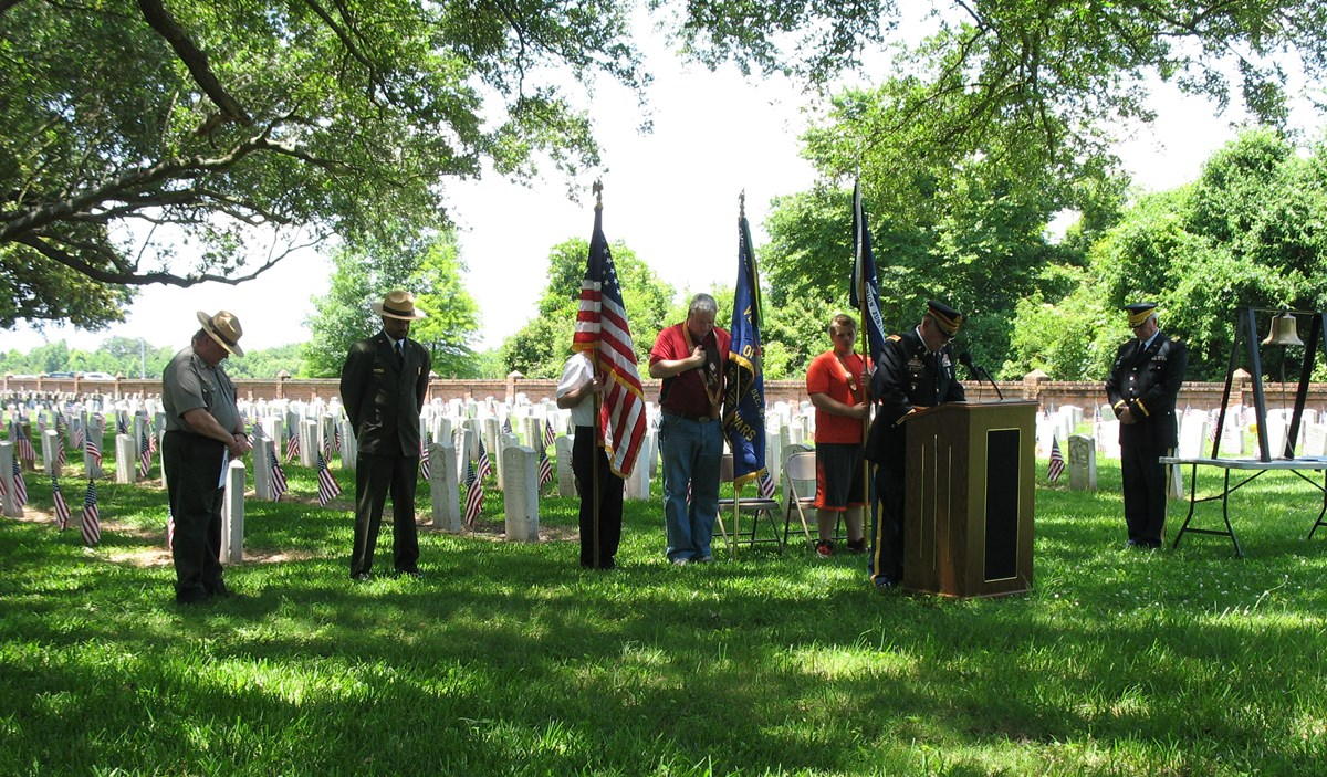 Image of people with bowed heads during Memorial Day ceremony at Chalmette National Cemetery