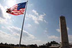 A large, fifteen star American flag from the War of 1812 flies beside the Chalmette Monument, a memorial obelisk