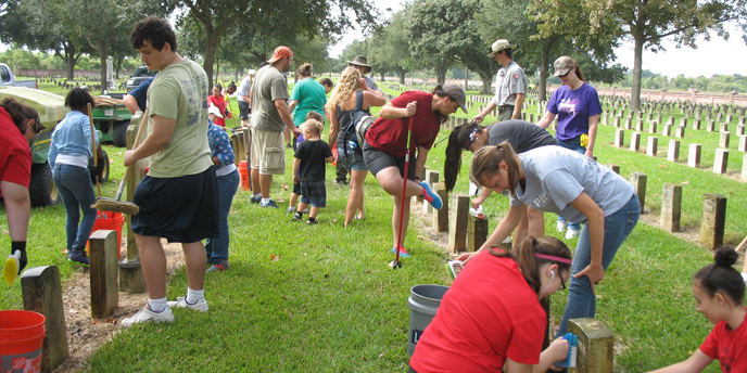 Image of volunteers cleaning headstones at Chalmette National Cemetery