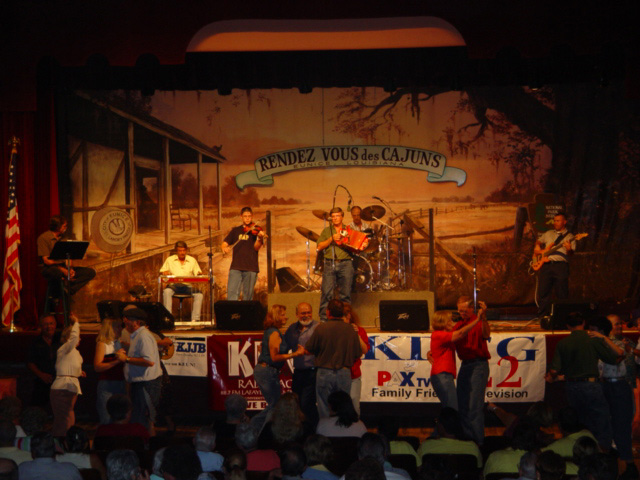 Image of people dancing in front of a stage where a Cajun band is playing