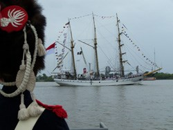 A reenactor in a French uniform of the War of 1812 watches a three masted sailing ship pass on the Mississippi River