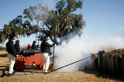 U.S. Navy reenactors of the War of 1812 fire a naval cannon at the Chalmette Battlefield
