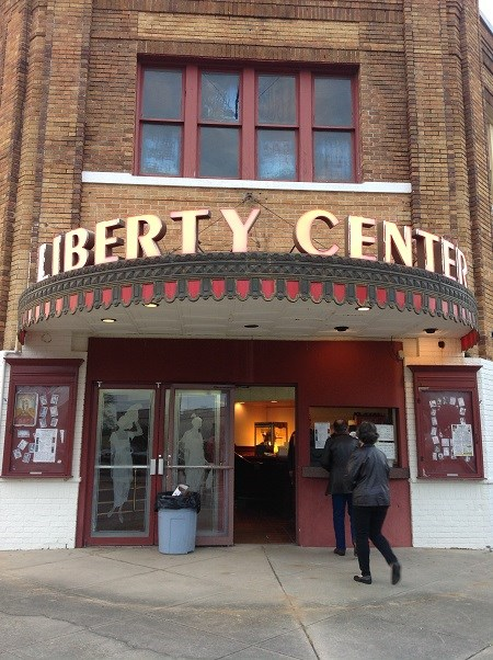"A man and a woman approach the ticket window of a theater building, under a lighted sign reading ""Liberty Center"""