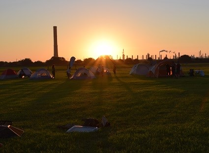 seven tents in an open field at sunset
