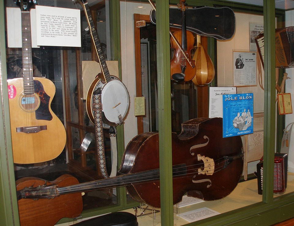 Display case with guitar, banjo, accordion, and other instruments
