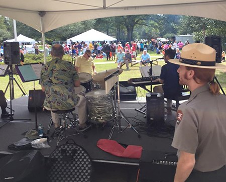 A park ranger stands backstage as a band plays beneath a tent.