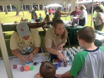 Two Centennial Volunteer Ambassadors assist a young park visitor to construct a craft project with colored beads