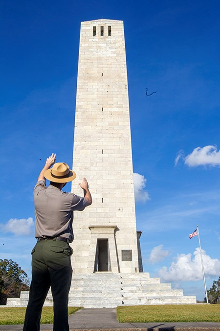 ranger with back turned to us pointing to chalmette monument