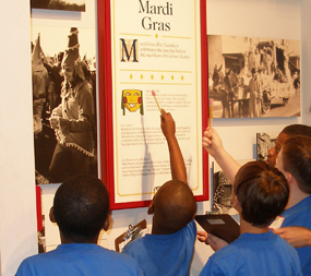 Boys in school uniforms look at a display in the Acadian Cultural Center