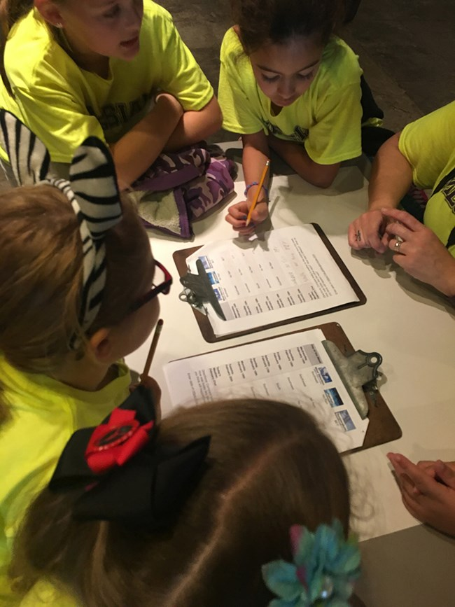 Students around a table writing on clipboards