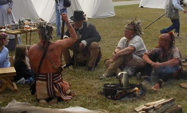 Men dressed as 1815-era Choctaw Indians talk to girls at living history event