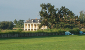 A plantation house, trees, and cannon at Chalmette Battlefield
