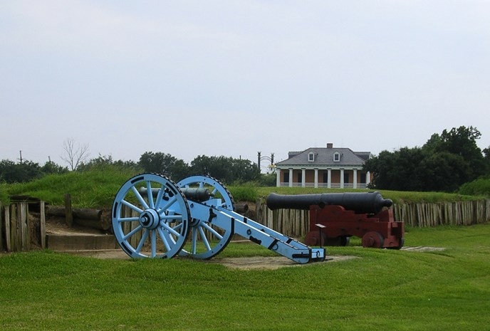 Image of War of 1812 cannons, rampart, and historic house at Chalmette Battlefield