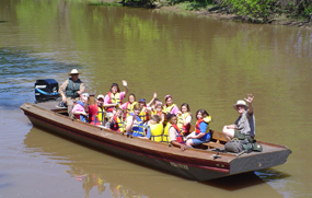 Children and a park ranger wave from a traditional wooden boat during a bayou tour