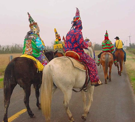 adults in colorful rompers with decorative cone shaped hats, ride horses