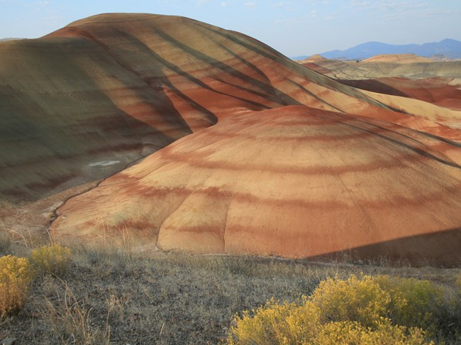 Photograph of the painted hills, weathered rocky hills with alternating tan and rust colored layers.