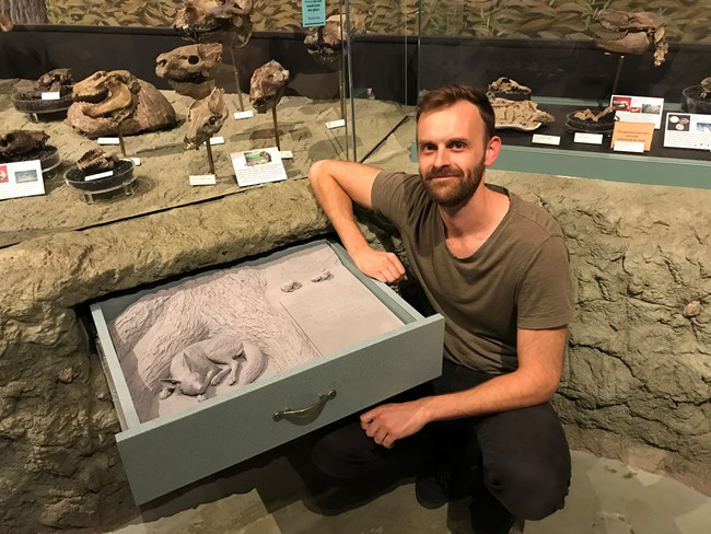 Artist Reid Psaltis sits near his artwork of a sculpted dog in an exhibit drawer.