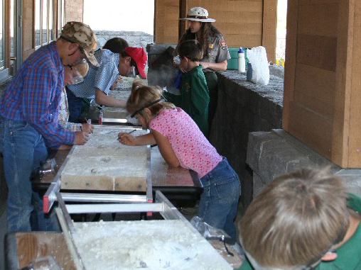 Teachers work with students in a simulated fossil dig.