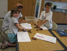 Two children and an adult enjoy coloring, stamping, and learning together while seated at a table in the Junior Ranger room of the visitor center.