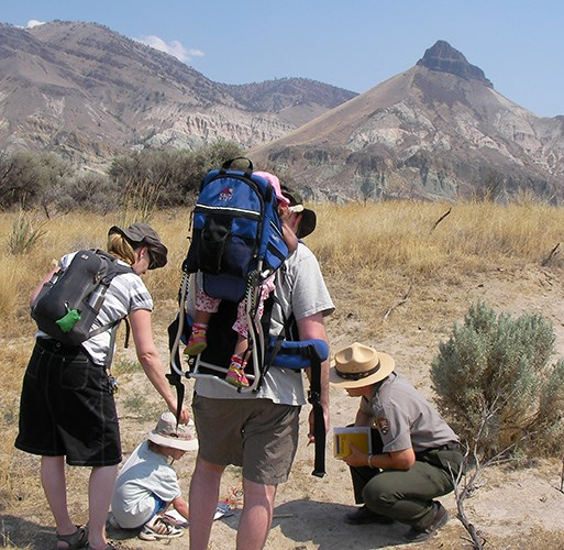 A ranger shows a young visitor fossils found in the area while parents look onward. One of the parents has a baby on his back riding in a carrier. Sheep Rock is seen in the distance.